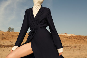 woman wearing coat and covering her face with r turtleneck  sweater at beach