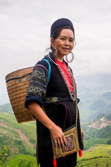 Smiling elderly woman from Northern Vietnam with basket on back