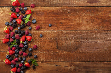 Ripe and sweet berries on wooden background
