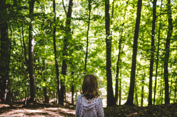 Young girl standing in the green woods