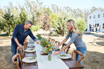 Mature couple setting the table for a farm to table dinner party