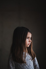 Profile portrait of pretty young girl against a neutral background
