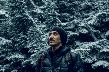 Male explorer into the forest during the snowfall