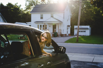 Child leaning out an open car window and looking back