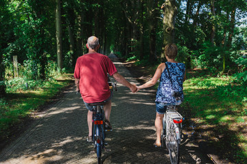 Middle age couple riding bikes and holding hands in The Netherla