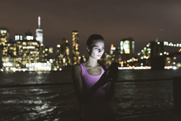 Young woman using technology at night against New York skyline