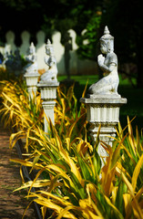 Statues of Budda in the garden among yellow leaves