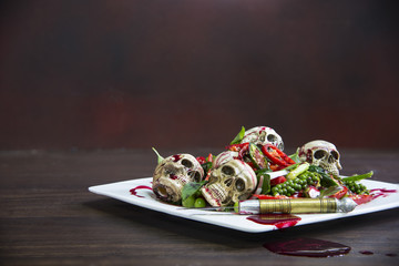 Stir-fry skulls with chili and pepper with blood on the wooden table, Halloween day food.