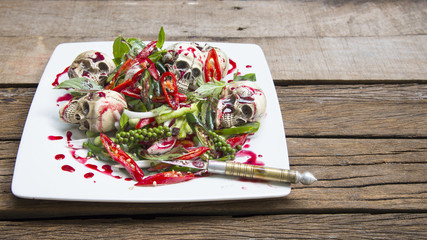 Stir-fry skulls with chili and pepper with blood on the wooden table, Halloween day food, Selective focus.