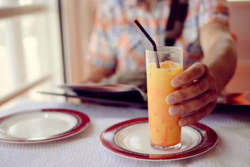 Glass of refreshing cool mango lassi sweet Indian drink over restaurant table light background