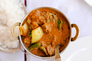 Closeup on Indian speciality curry dish over light restaurant table background. Traditional maincourse delicacy