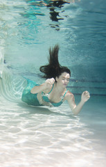 Model underwater in a pool wearing a mermaids tail.