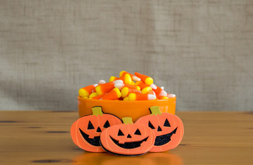 candy corn in an orange bowl with 3 cartoon jack-o-lanterns on a wooden table