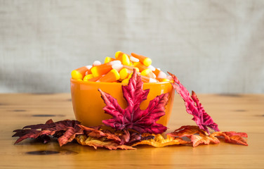 candy corn in an orange bowl with colorful autumn leaves on a wooden table
