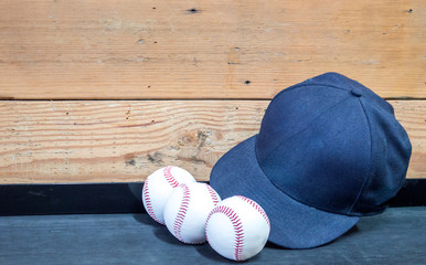 3 baseballs and a blue baseball cap on a black shelf against a wooden wall
