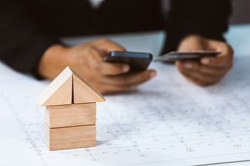Close-up of house architectural model with businessperson holding credit card and using mobile above project house draw plan