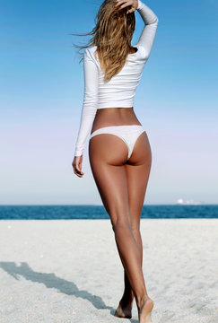 Beautiful tanned woman in a white swimsuit on the beach.