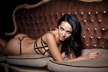 Gorgeous girl in a sexy black lingerie on sofa