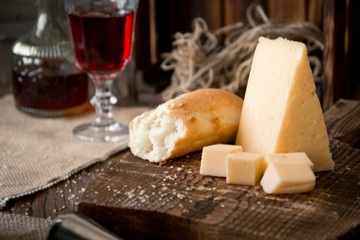 Cheese and bread on the wooden board and red wine. Rustic style