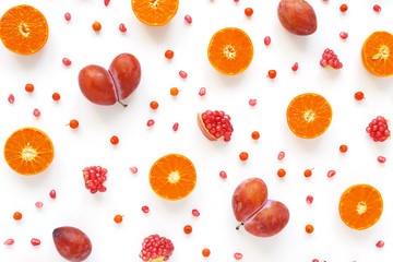 Pattern of fresh fruits. Food background. Top view, flat design. Collage of plum in the form of heart, slices of mandarins, grains of pomegranate.