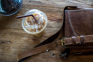 leather bag With iced coffee On a wooden desk