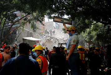 A woman holds up a tool for rescue workers who are searching for people under the rubble of a collapsed building after an earthquake hit Mexico City