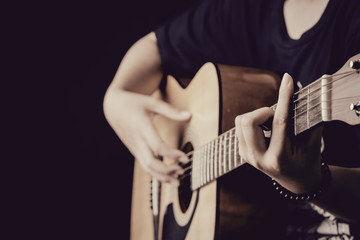 close up of woman hands playing guitar in the dark background,vintage style