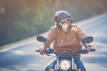 filter and grain photo ; man riding motorbike on a road in freedom lifestyle at vacation time