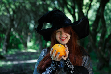 Photo of smiling witch with pumpkin