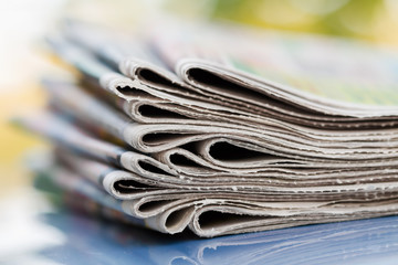 Time to read concept. Newspapers folded and stacked on the blue surface and blur background. Closeup, selective focus