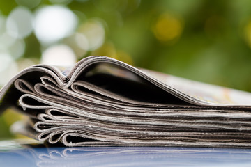 Time to read concept. Newspapers folded and stacked. One top newspaper is open. Closeup, selective focus.