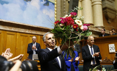 Outgoing Swiss Foreign Minister Burkhalter of the FDP waves with a bunch of flowers at Swiss parliament in Bern