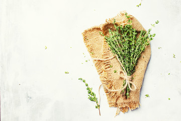 Fresh thyme on canvas napkin, gray background,  top view