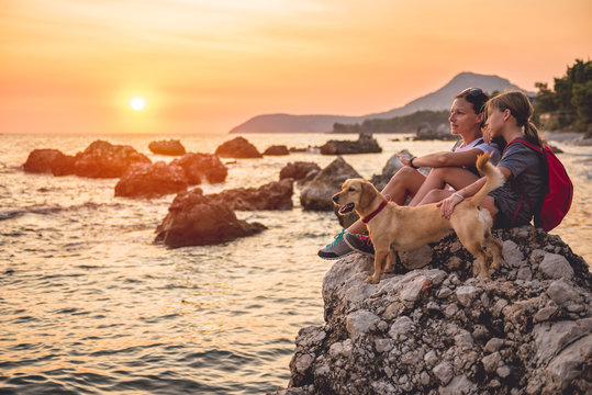 Mother and daughter with a dog hiking along the seashore