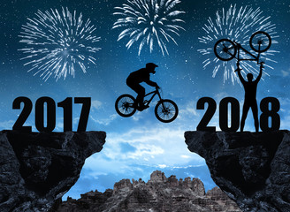 Silhouette cyclist jumping into the New Year 2018, in the background night sky with fireworks.