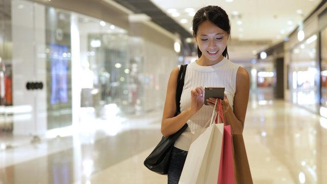 Shopping woman using smart phone at shopping center