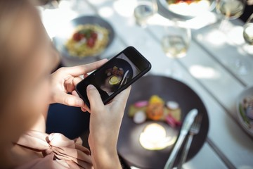 Woman taking picture of food in restaurant