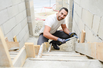 young man mason demolding concrete stairs with hammer in a new house construction site