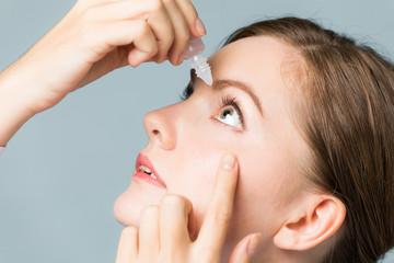 Young woman applying eye lotion.