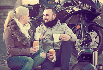 couple posing near motor bike with sandwitches and coffee