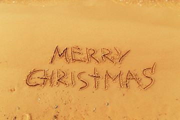 """The inscription """"Merry Christmas"""" on the sand."""