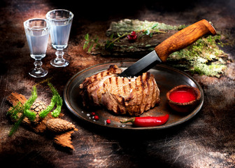 Wall Mural - Beef steak entrecote barbecue and hunting knife on a dark textured background