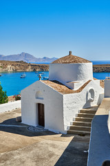Fotobehang Cyprus Small building of Christian church located on embankment of calm blue sea on sunny day in coastal town