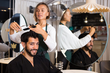 hairdresser working with scissors and comb