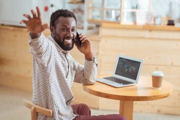 Overjoyed man greeting someone while talking on phone