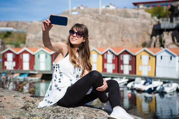 Young and happy tourist woman sitting in the harbor in Smogen town, Sweden, taking a photo of herself with mobile device.