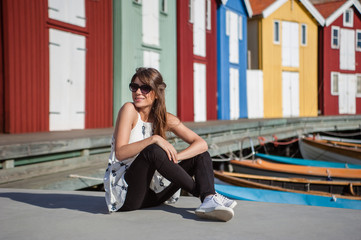 Young and happy tourist woman sitting in the harbor in Smogen town, Sweden. Beautiful traditional colorful wood houses on the background.