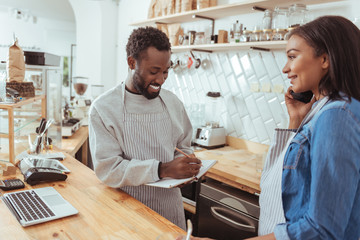 Smiling barista putting down order made by phone