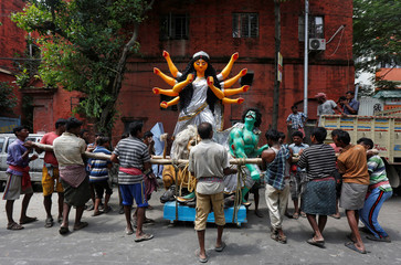 Labourers prepare to load an idol of the Hindu goddess Durga onto a truck to transport it to a pandal for the upcoming festival of Durga Puja in Kolkata