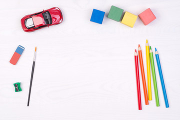 Kid's desk with colorful pencils and toys, top view with copy space